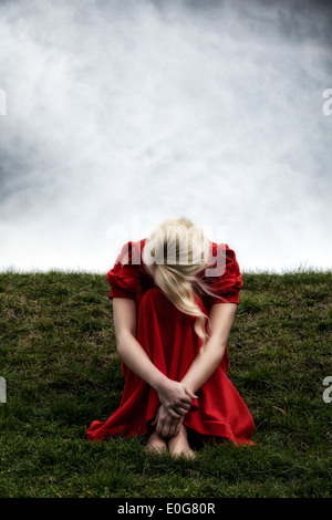 a woman in a red dress is sitting on a hill - Stock Photo