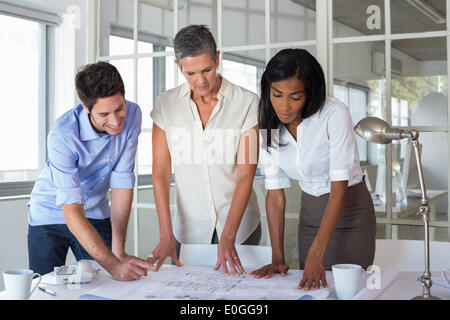 Team of architects looking at blueprints - Stock Photo