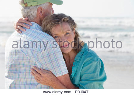 Happy senior couple hugging on sunny beach - Stock Photo