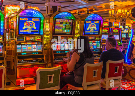 A couple playing the slot machines in the Casino of the Wynn Hotel Las Vegas Nevada - Stock Photo