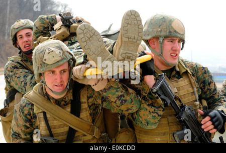 Marines assigned to Fleet Antiterrorism Security Team Company Pacific, 2nd Platoon, carry a casualty on a stretcher - Stock Photo