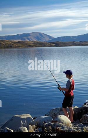 Boy fishing, Lake Ohau, Mackenzie Country, South Canterbury, South Island, New Zealand - Stock Photo