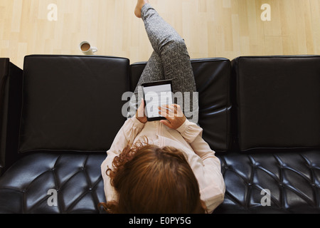 Top view of young brunette using digital tablet while sitting on a couch. Female reading a book - Stock Photo