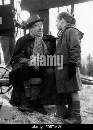 Actor Fernandel talks with girl on set of film - Stock Photo