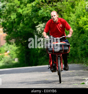 Royal Mail postman on a bicycle with a basket and side pannier carrying letters riding up a steep hill in Manningtree,Essex,UK - Stock Photo