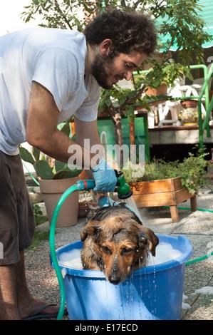 Man washing dog in the garden - Stock Photo