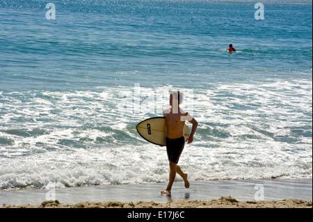 Surfer running on beach at Laguna Beach, CA - Stock Photo
