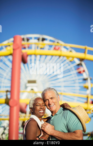 Portrait of happy senior couple hugging at amusement park - Stock Photo