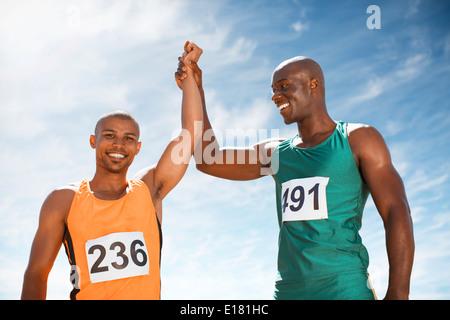 Athletes celebrating together on track - Stock Photo