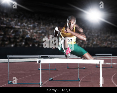 Runner clearing hurdle on track - Stock Photo