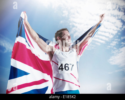 Track and field athlete holding British flag and celebrating - Stock Photo
