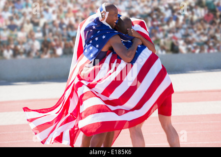 Track and field athletes wrapped in American flag on track - Stock Photo