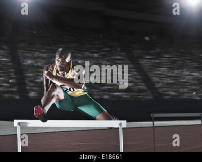 Runner jumping hurdle on track - Stock Photo