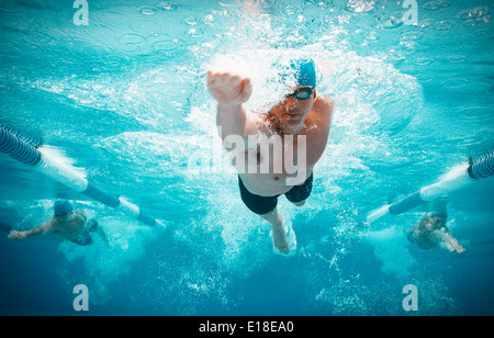Swimmers racing in pool - Stock Photo