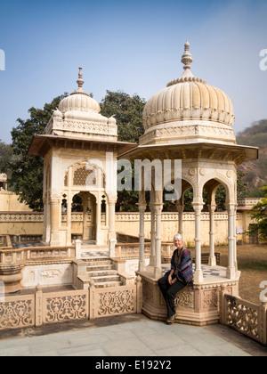 India, Rajasthan, Jaipur, Gaitore Ki Chhatriyan, Royal Family Cremation Ground visitor sat on memorial - Stock Photo