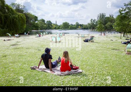 Young couple sitting amongst the daisies in Regent's Park, London, England, UK - Stock Photo