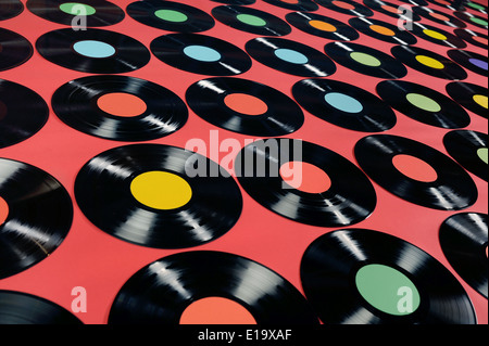 Colorful collection of vinyl records on red background, angle view, editable labels, the image is suitable for background - Stock Photo