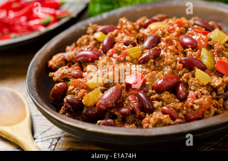 A hearty bowl of chili con carne with hot peppers. - Stock Photo