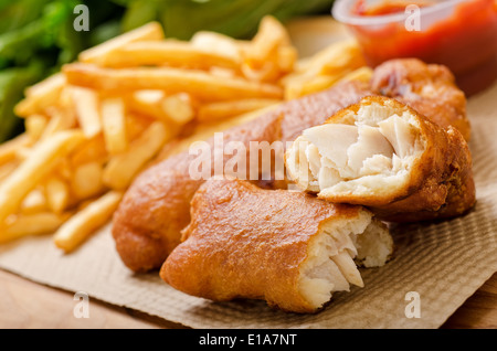 A delicious crispy battered deep fried fish and chips with greens and ketchup. - Stock Photo