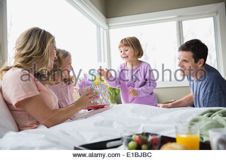 Daughters bringing gift to mother in bed - Stock Photo