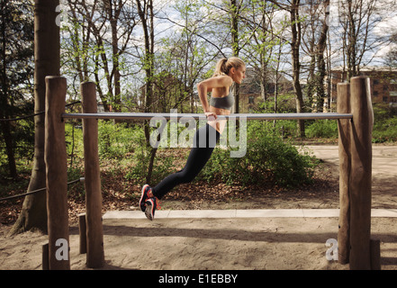 Strong and physically fit young woman doing triceps dips on parallel bars at park. Caucasian fitness female exercising - Stock Photo