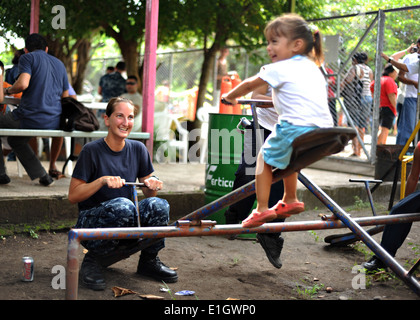 U.S. Navy Hospital Corpsman 3rd Class Jennifer Nuehring, left, plays on a teeter-totter with a child at the Escuela - Stock Photo