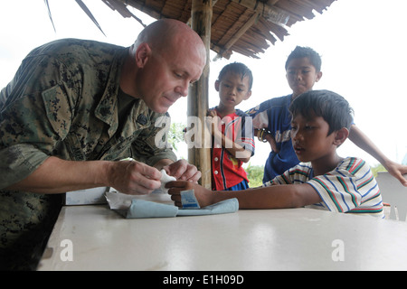 U.S. Navy Hospital Corpsman 1st Class Johnathan Akers, left, performs a medical procedure on a Filipino boy?s hand - Stock Photo