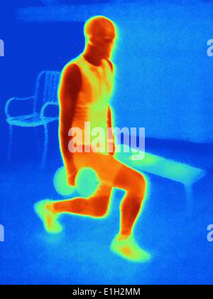 Thermal image of young man training with barbells. The image shows the heat produced by the muscles - Stock Photo