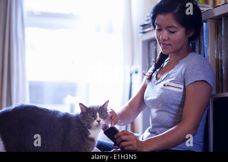 Young woman holding cellular phone stroking cat - Stock Photo