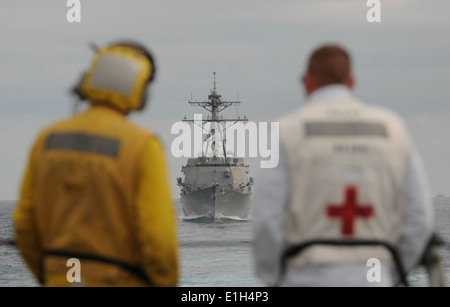 U.S. Navy Boatswain?s Mate 3rd Class Jeffrey Rashley, left, and Hospital Corpsman 1st Class Robert Williamson look - Stock Photo