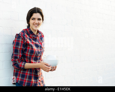 Portrait of smiling young woman holding crockery - Stock Photo
