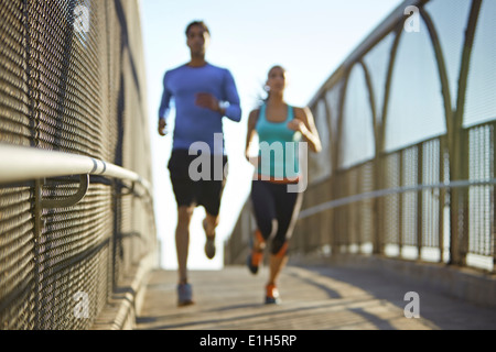 Man and woman running over bridge - Stock Photo