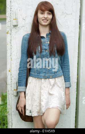 Portrait of young woman leaning against wall - Stock Photo