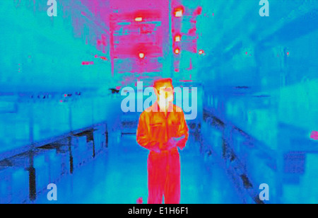 Infra red heat image of warehouse worker in factory - Stock Photo