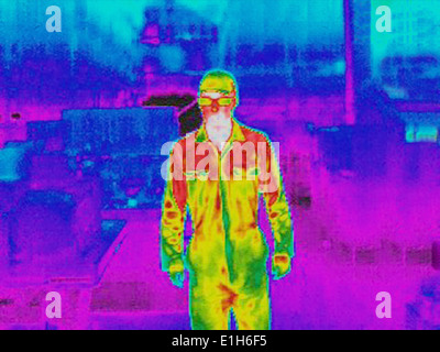 Infra red heat image of worker in factory - Stock Photo
