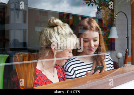 Young women through window, looking at smartphone - Stock Photo