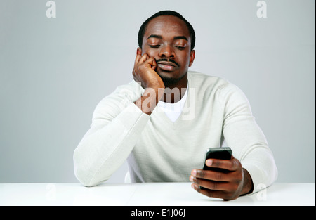 Pensive african man using smartphone on gray background - Stock Photo
