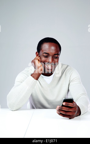 Cheerful african man sitting at the table and using smartphone - Stock Photo