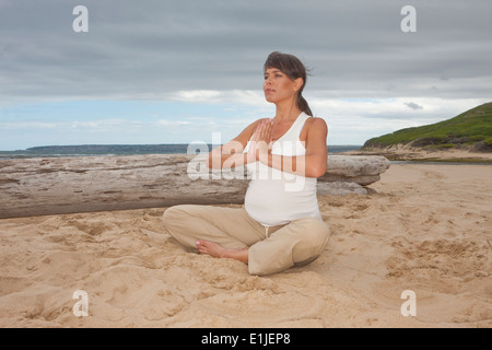 Pregnant mid adult woman practicing yoga on beach - Stock Photo