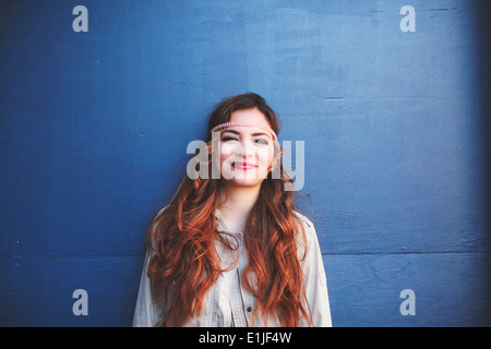 Portrait of young woman leaning against blue wall - Stock Photo