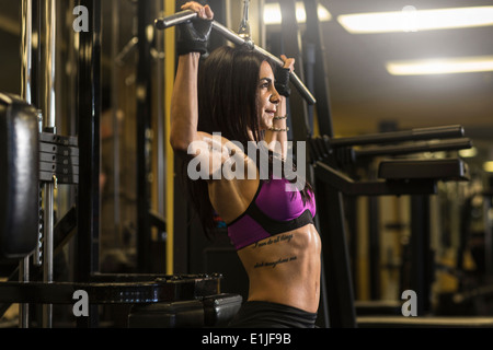 Mid adult woman in gym doing pectoral exercise - Stock Photo