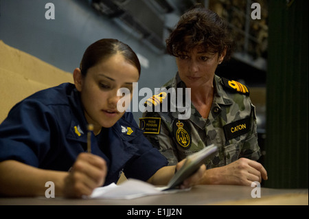 U.S. Navy Hospital Corpsman 1st Class Laura Blanco, left, fills in passport information for Royal Australian Navy - Stock Photo