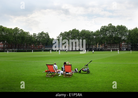 A couple watching a cricket match in Vincent Square, Westminster, London. UK. This sports venue belongs to Westminster - Stock Photo