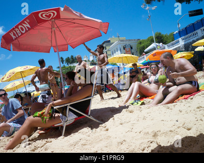 SALVADOR, BRAZIL - OCTOBER 13, 2013: Locals mix with tourists relaxing on a bright summer afternoon on Porto da - Stock Photo