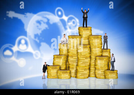 Composite image of business people on pile of coins - Stock Photo