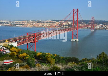 The 25 de Abril Bridge is a suspension bridge connecting the city of Lisbon to the municipality of Almada, over - Stock Photo