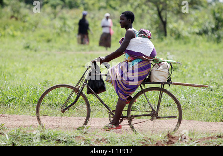 A mother and her baby cycle in a rural part of the Lira district of northern Uganda. - Stock Photo