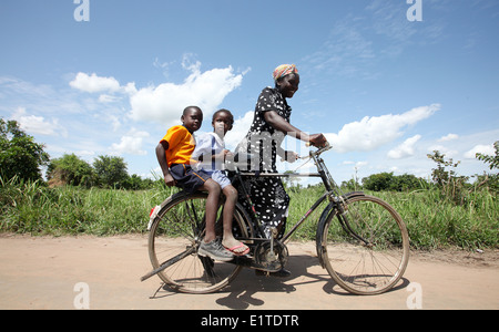 A mother and her two children cycle in a rural part of the Lira district of northern Uganda. - Stock Photo