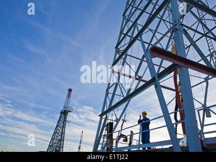 Drilling rig worker talking on radio on platform. - Stock Photo
