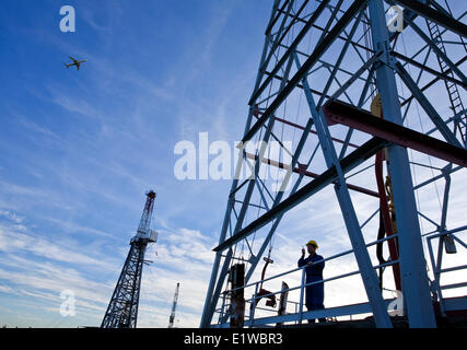Drilling rig worker talking on radio on platform with airplane flying overhead, Alberta, Canada - Stock Photo